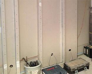 Des profilés en aluminium et des plaques de placoplâtre constituent la base des compartiments muraux.