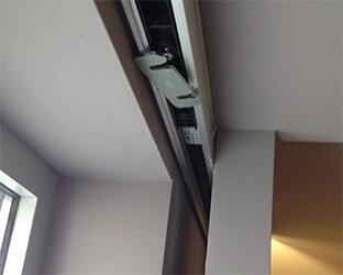 Le rail de la porte coulissante automatique disparaît dans le compartiment du mur.