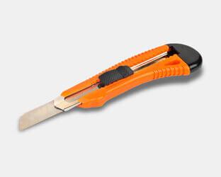 Ein Cutter Messer (Universalmesser) mit langer, scharfer Klinge zum Schneiden des Akustikschaums.
