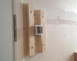 Des bois équarris le long des interrupteurs forment la base sur laquelle le couvercle est ensuite vissé à travers le tissu.