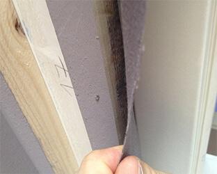 Une bande de tissu acoustique est collée sous le bois équarri de manière à ce qu'elle dépasse vers l'extérieur.