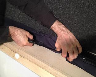Le cadre de l'écran est fixé avec la spatule dans les profils de tension.