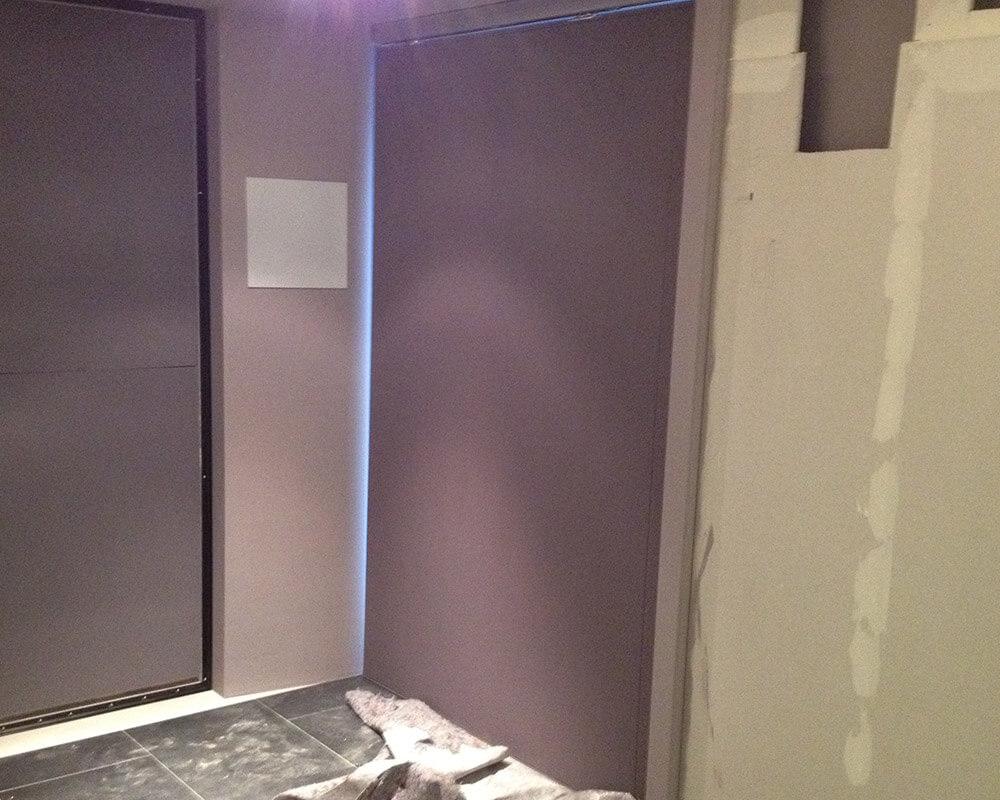 La porte coulissante entièrement recouverte de tissu acoustique dans le home-cinéma
