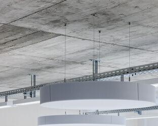 Runde Akustiksege werden über ein Hängesystem an der Decke befestigt.